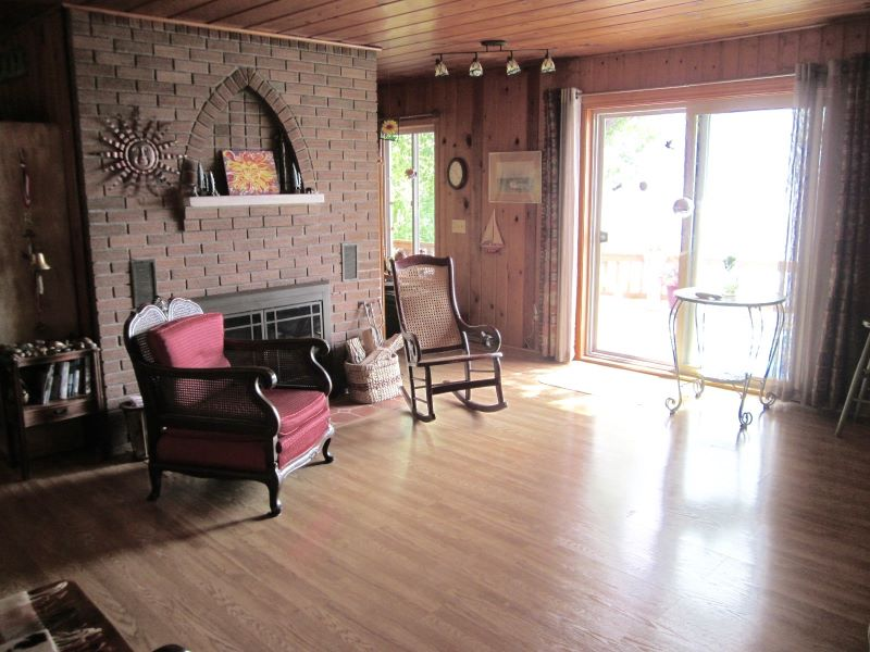 A photo of the living room with wood burning, fireplace.